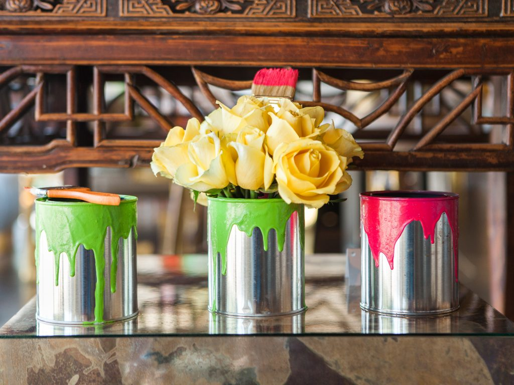 Colorful paint cans and yellow roses