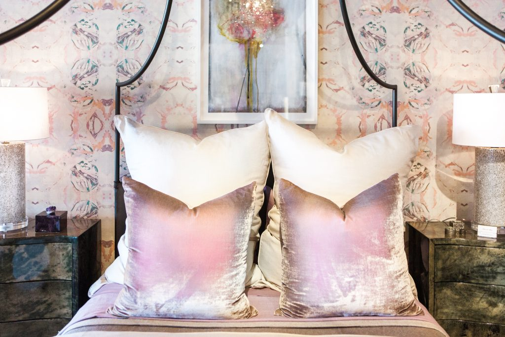Large pillows in lavender and cream on a canopy bed