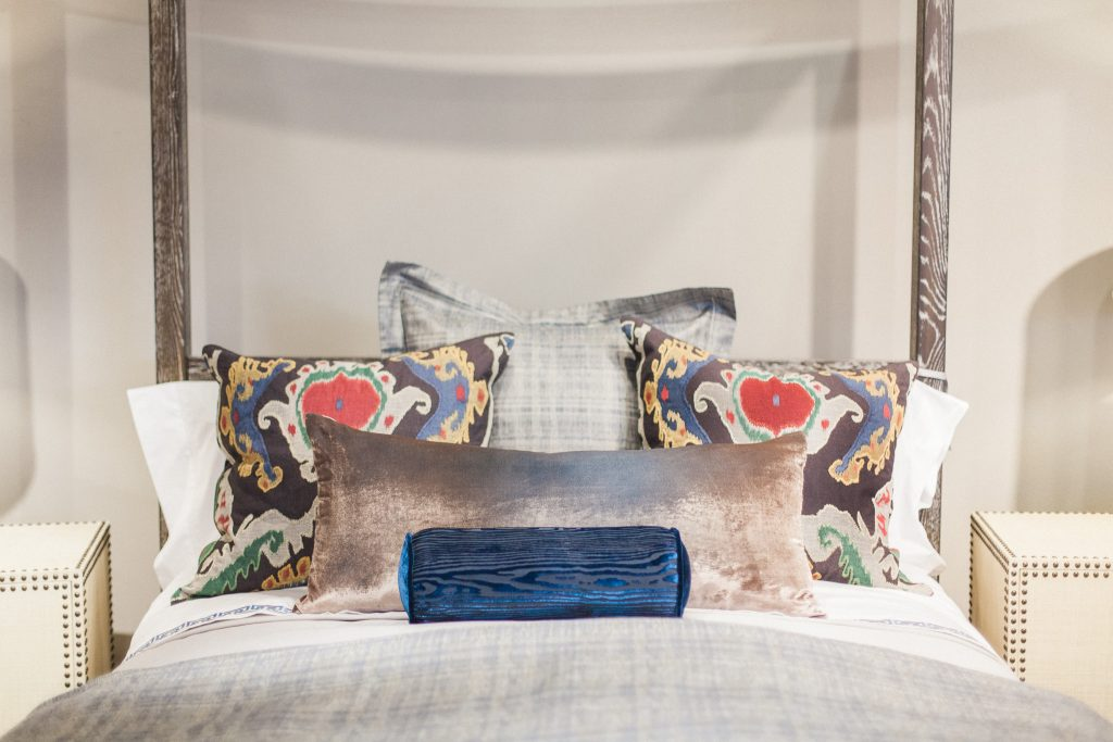 Bedding design by Margaret Chambers with brightly colored accent pillows atop a softly neutral bed