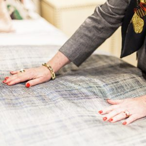 Margaret Chambers smoothing the top of her bedding design