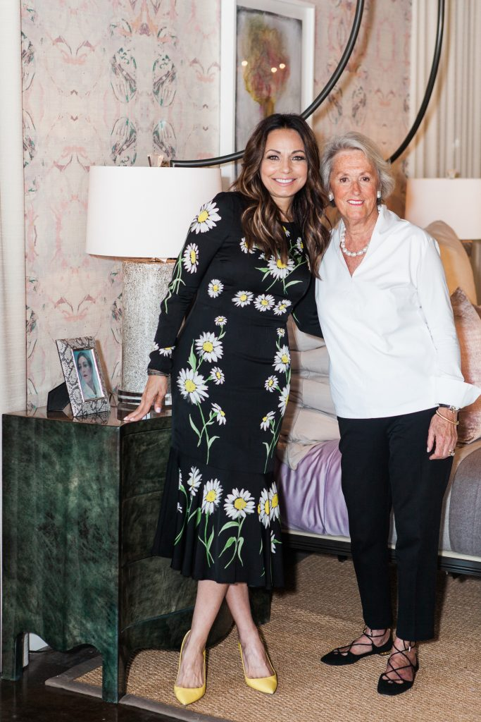 Moll Anderson and Mary Ella Gabler pose in front of a bed