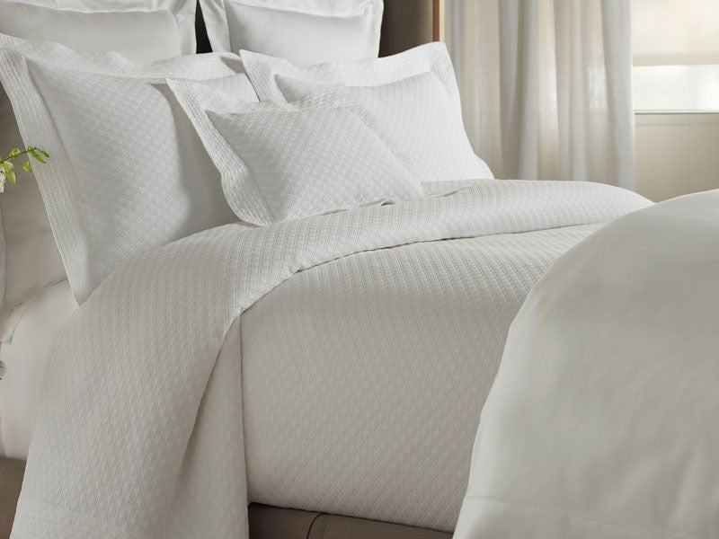 All white bed dressed in a diamond matelassé pattern