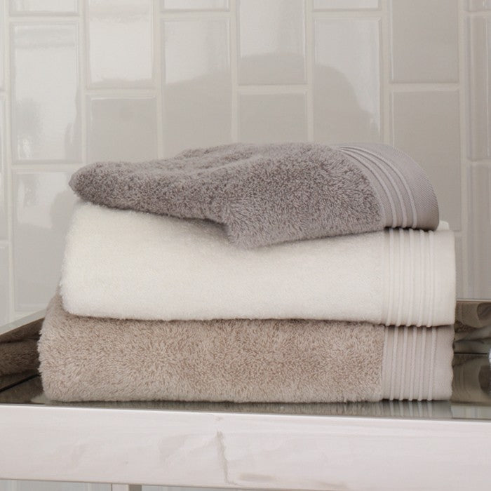 A stack of folded luxury bath towels in various neutral shades