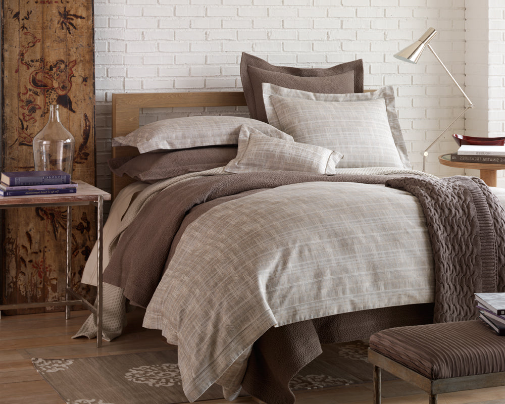 A modern bed dressed in neutral tones with a variety of textures and patterns