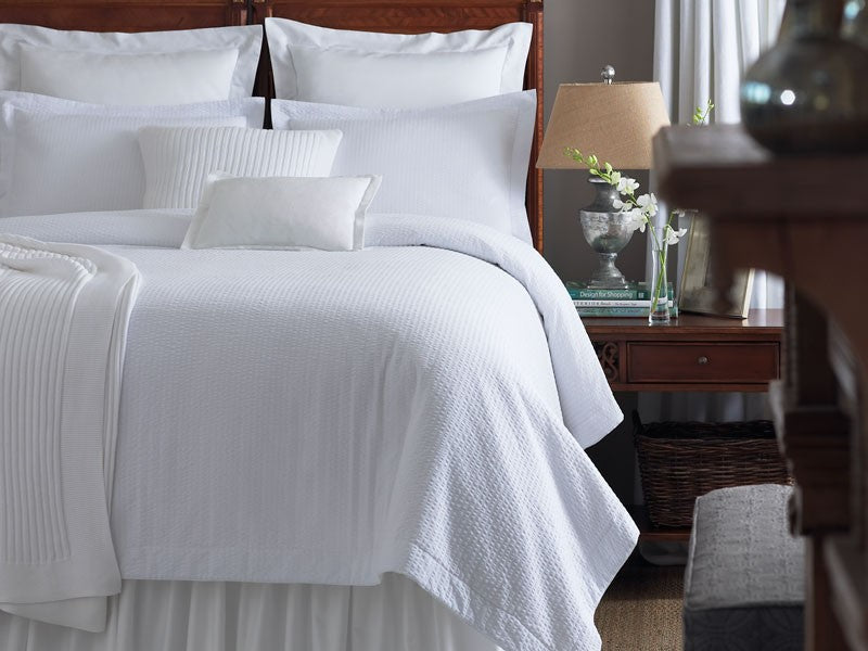 An all-white bed with rich textures