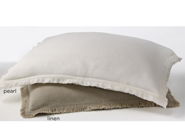 Pillow shams in pearl and linen colors with distressed fringe edging
