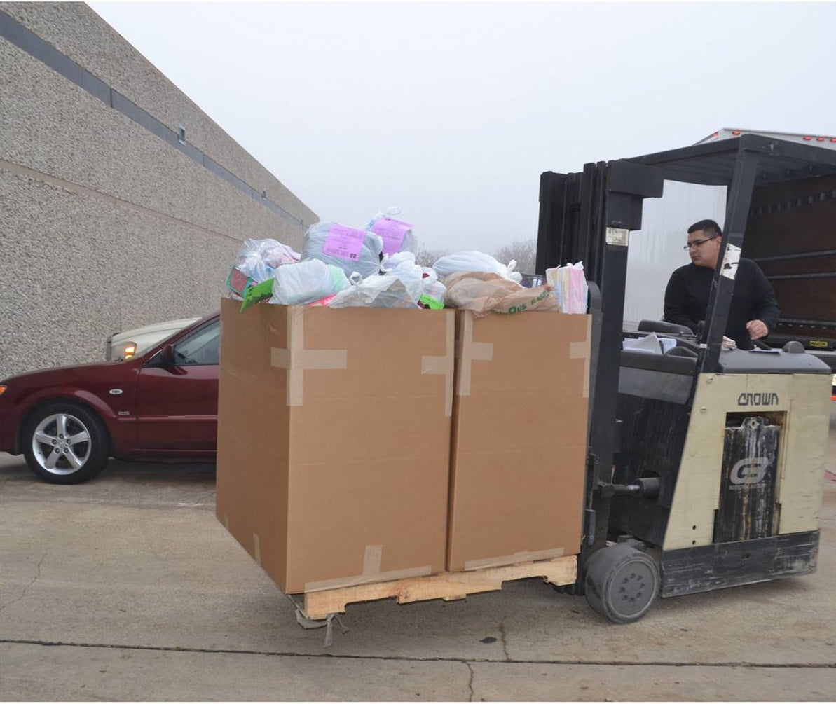 A worker moves a pallet full of donations for the Community Partners of Dallas toy drive