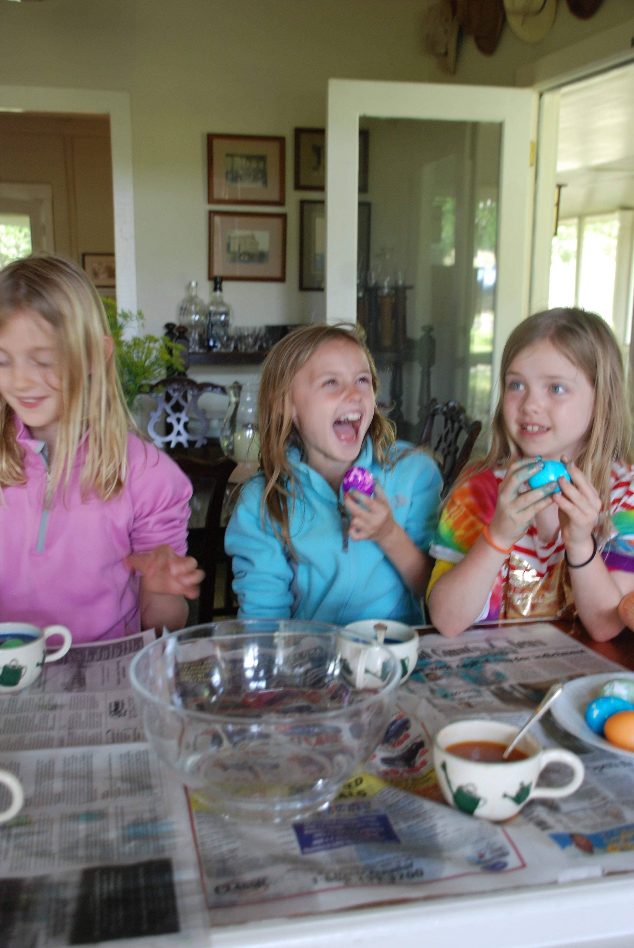 Girls laughing and having fun while dying eggs