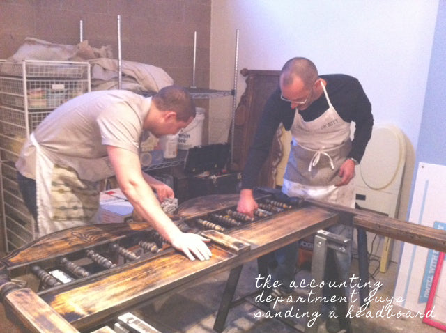 Two men working on sanding down a headboard to be refinished