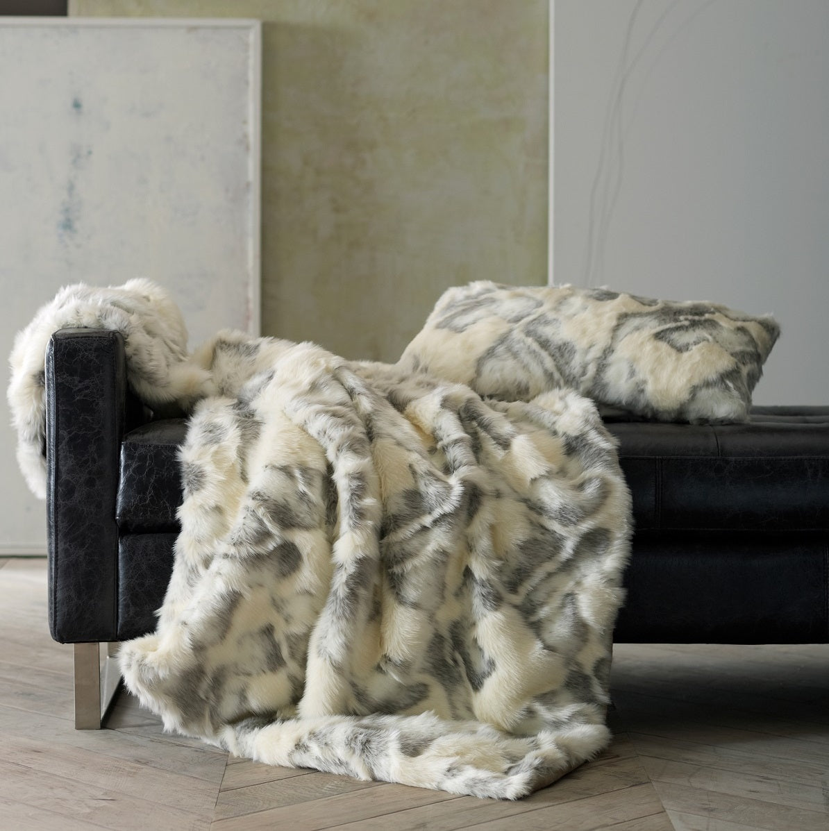 White and gray faux fur throw and pillow over black leather seating