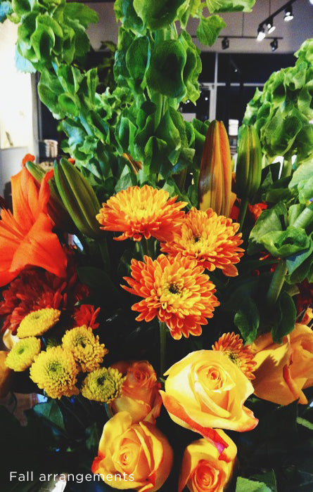 Fall flower arrangement with bright yellows and oranges amongst the greenery
