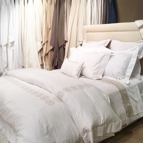 Luxury bed in white and linen with embroidered accents