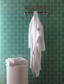 A monogrammed white robe hangs in front of a green tiled wall