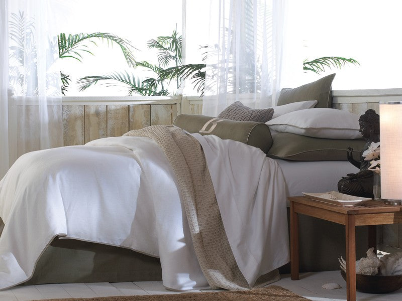 A bed in whites and neutrals with palm leaves in the background