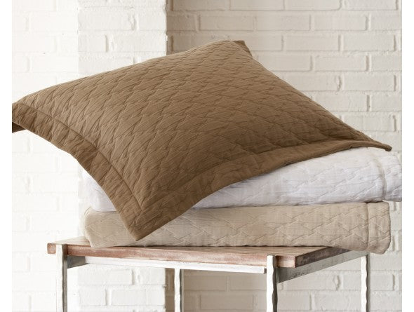 Matelassé coverlets and pillow sham in shades of white, cream, and brown
