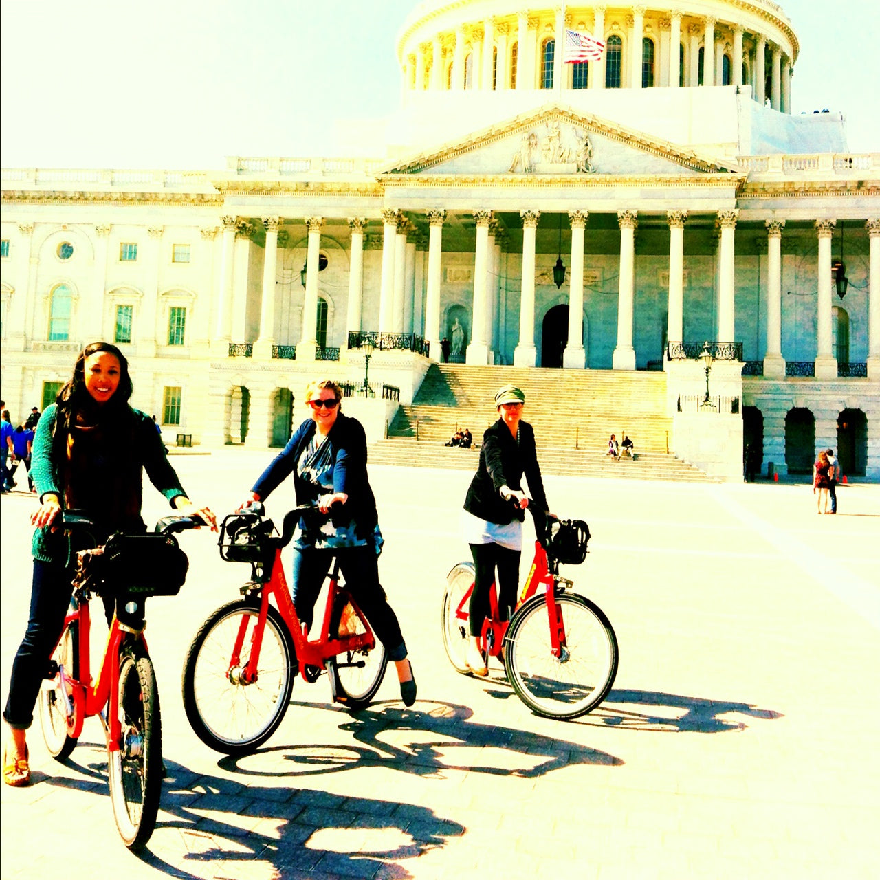 Three women riding rented bikes in front of the Capital building, in Washington, DC
