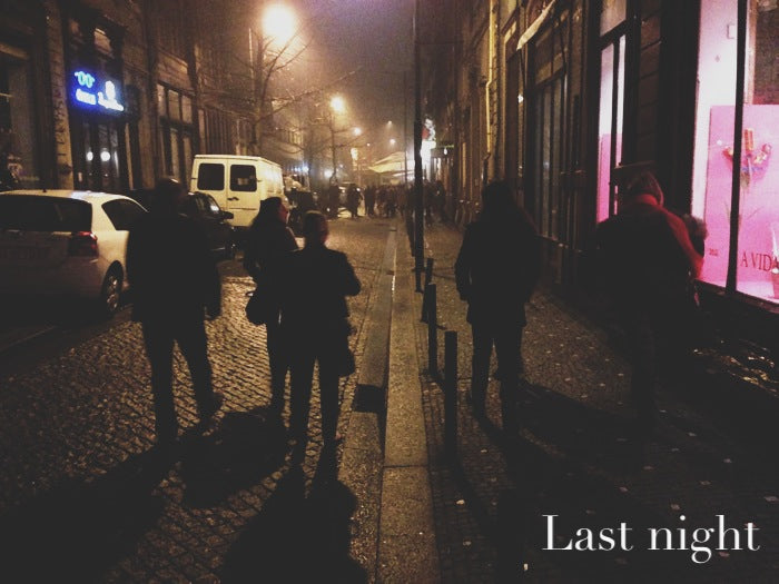 The team strolls down a cobbled street at night