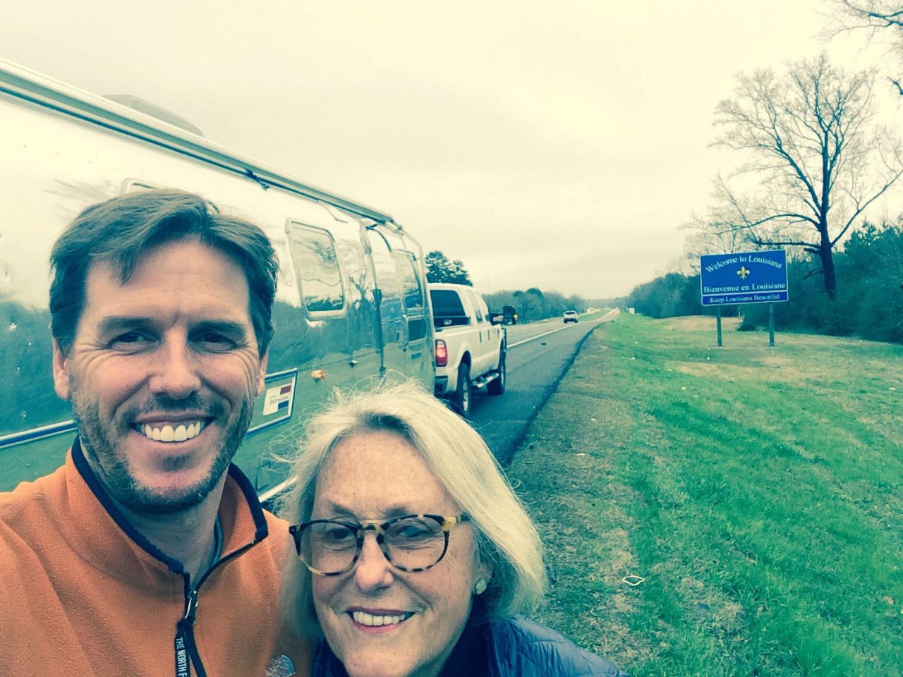 Josh Needleman and Mary Ella Gabler pose on the side of the highway with the Airstream and a Welcome to Louisiana sign in the background