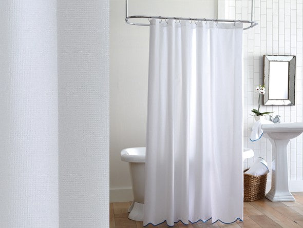 White pique shower curtain in a mostly white bathroom with black accents and scalloped bottom
