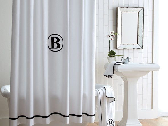 White pique shower curtain in a mostly white bathroom with black accents and monogramming