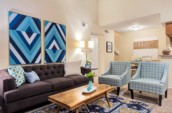 Beautifully designed living room in shades of blue and brown with abstract geometric art on the wall over the sofa