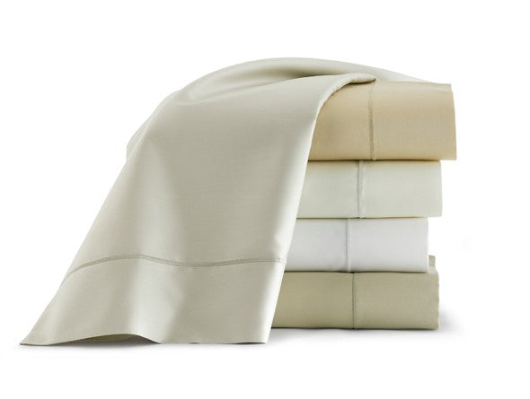 A stack of folded bed sheets, perfect for guests