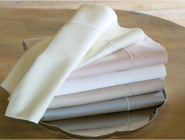 Stack of folded luxury sheets in various colors