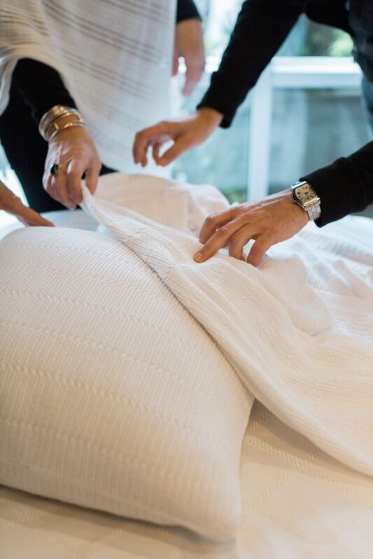 Hands of the designers examining Mirabelle Pillow and Throw
