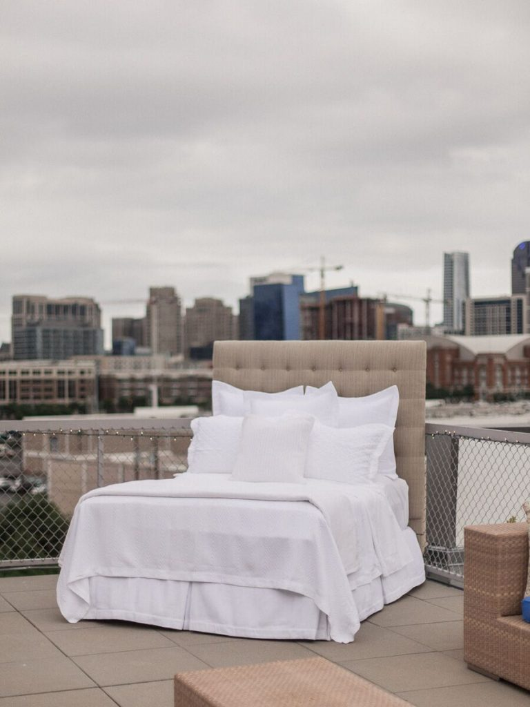 A well-dressed bed in white sits on a rooftop overlooking the Dallas skyline