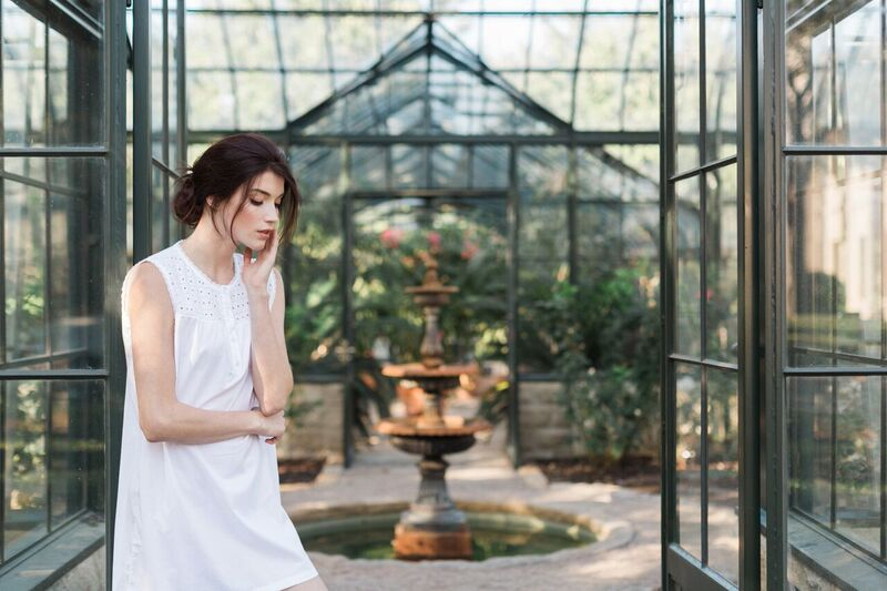 Model wearing white sleeveless night shirt inside a greenhouse with a fountain in the background