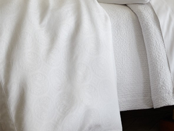 Detail of an all white bed with fine texturesin the duvet and coverlet
