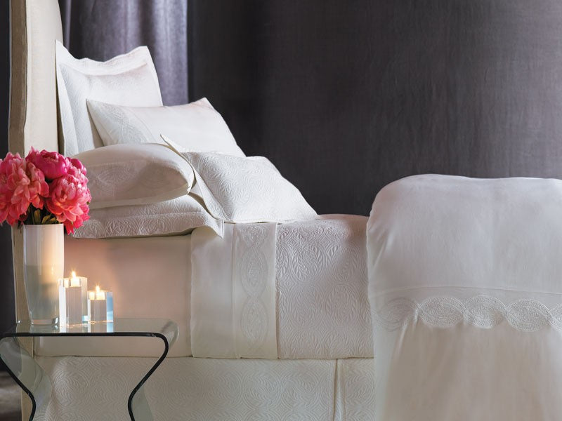 All white bedding featuring matelassé detailing next to a bouquet of bright pink flowers