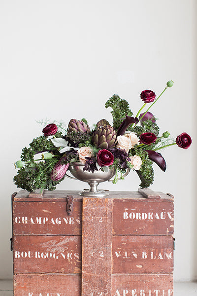 Fall floral and vegetable bouquet in shades of green, red, and purple, atop a wooden wine crate