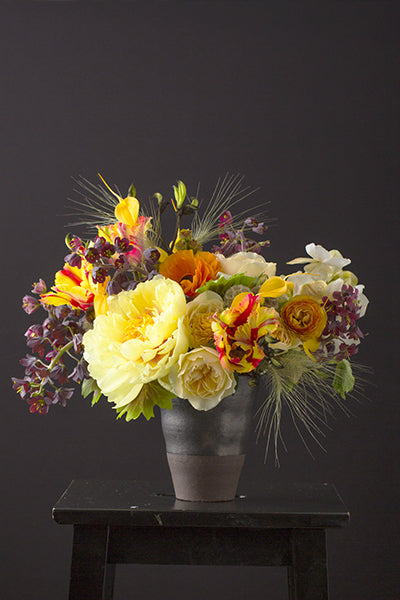 Floral arrangement featuring shades of yellow, white, and burgundy