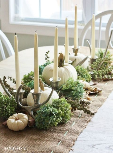 Fall centerpiece featuring white pumpkins and silver antlers atop greenery and a burlap table runner