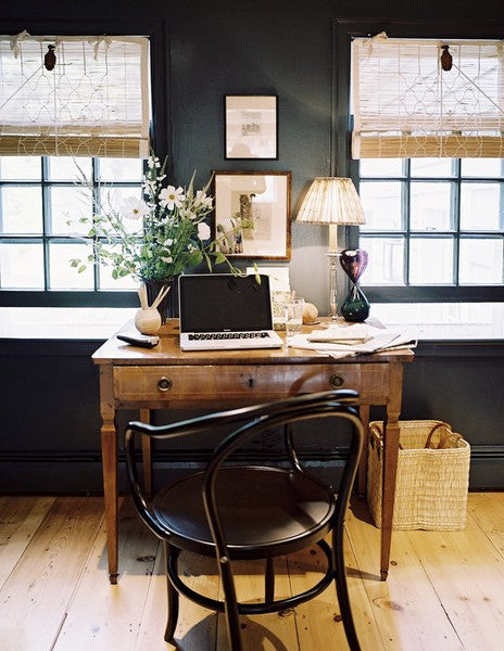 A beautifully appointed office with an antique desk, a fresh floral arrangement, and homey decor