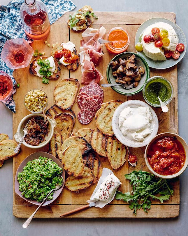 A serving board with the makings of a DIY bruschetta bar