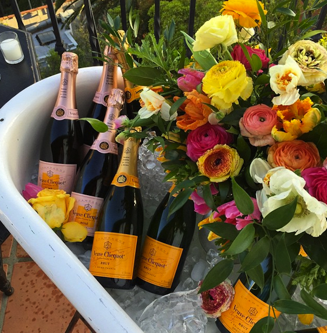 Bottles of Veuve Clicquot on ice surrounded by brightly colored flowers