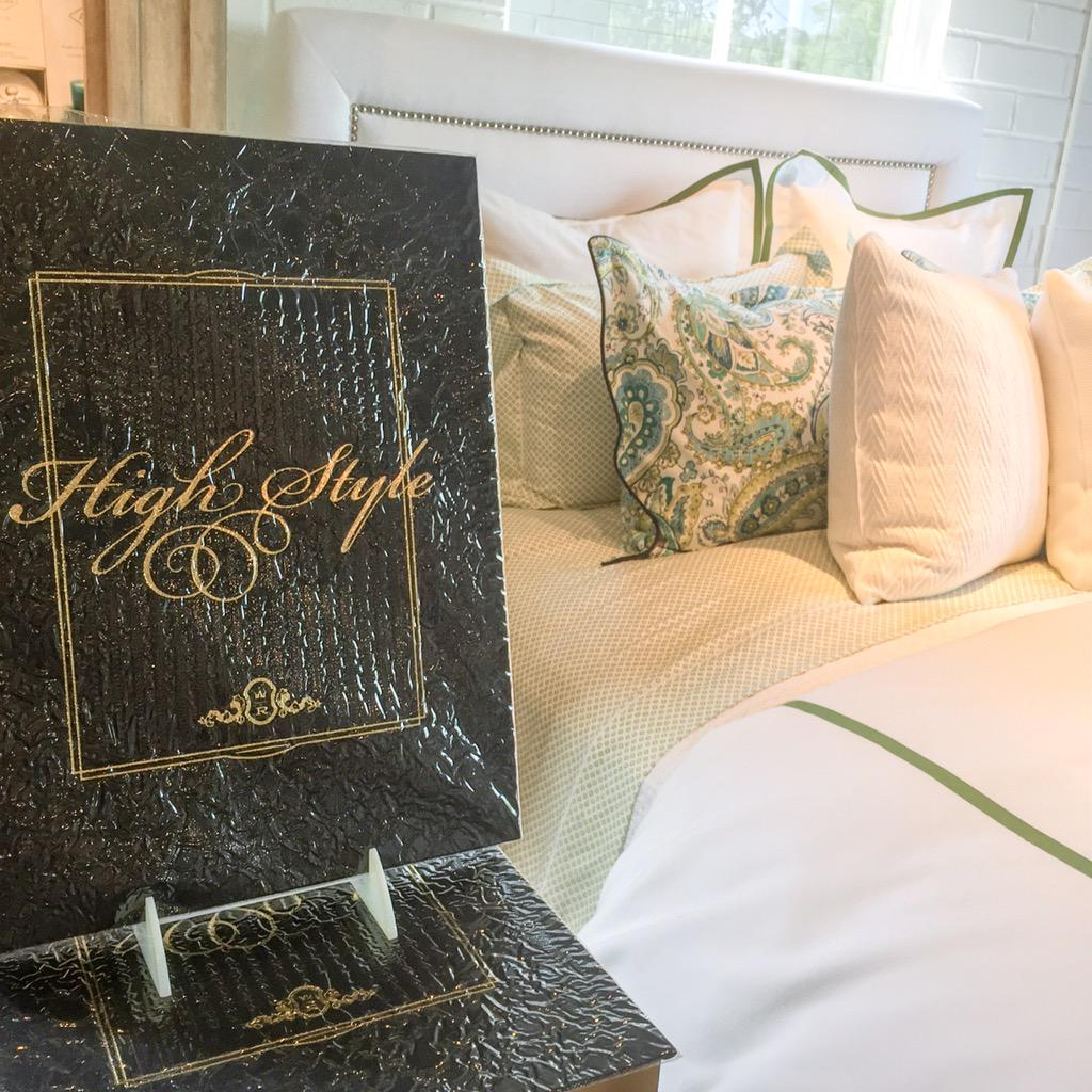 Copies of High Style on display next to a bed dressed in Peacock Alley linens