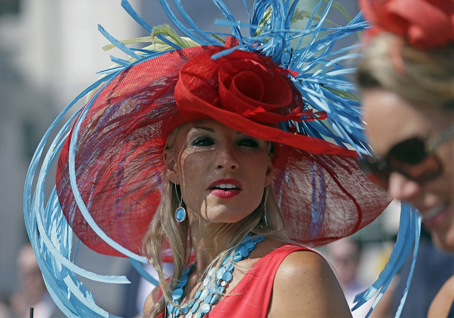 Nichole Whelan in a red hat with blue feathers for the Kentucky Derby