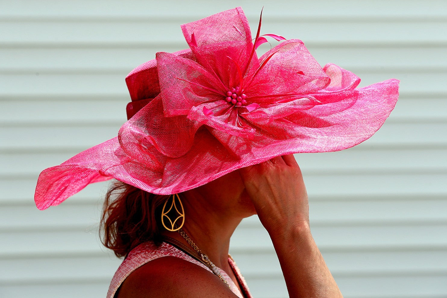 A woman wearing a bright pink hat with a large bow