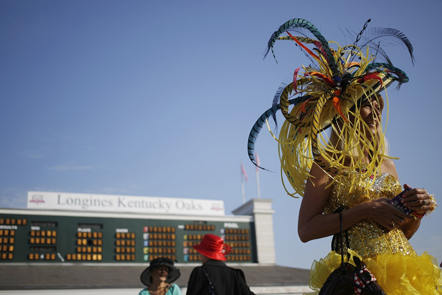 A woman in yellow wears an elaborate feathered hat for the Kentucky Derby
