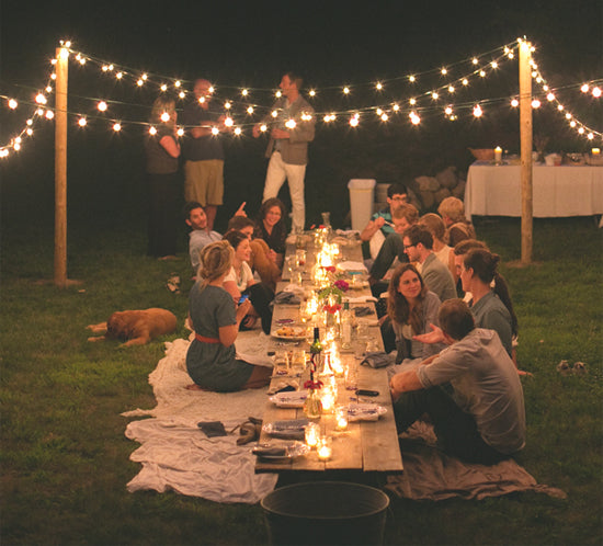 Guests at an outdoor party lounge around a low table with twinlke lights dangling overhead