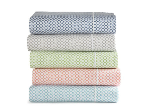 A stack of folded printed sateen sheets in various colors
