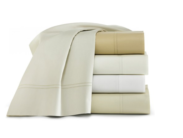 A stack of folded sheets in various neutrals
