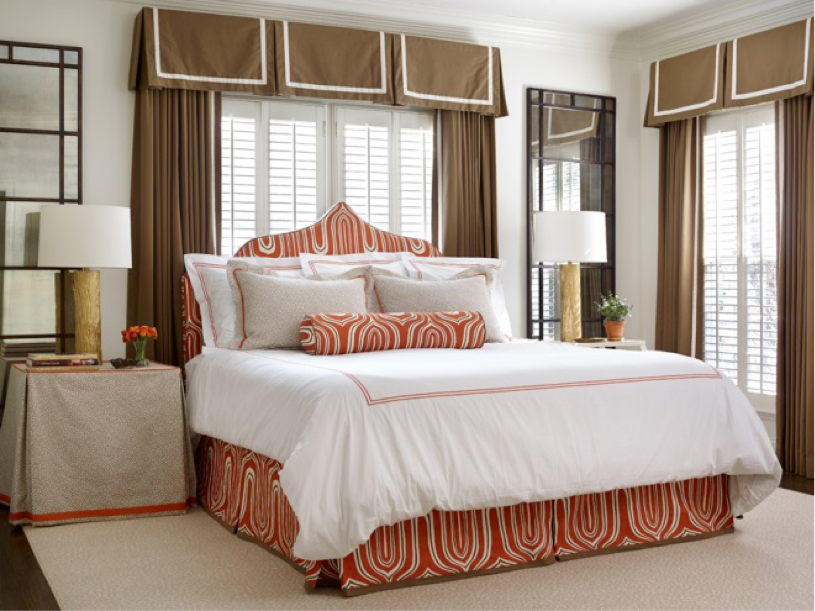 A beautiful bed styled in white with orange and tan accents