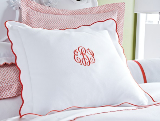 A pillow sham in white with a scalloped red edge and red monogram