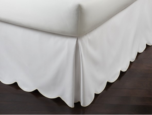 Corner of a scalloped bed skirt in white