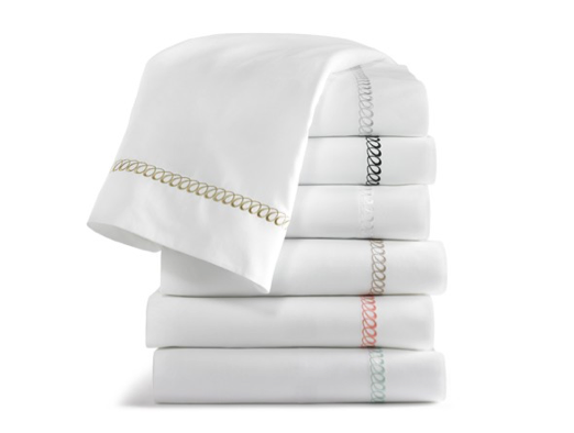 Folded white sheets with embroidered detailing in various colors