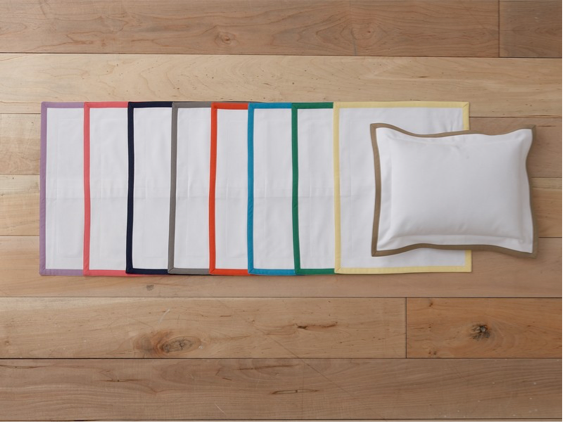White pillow shams with brightly colored edges against hardwood planks